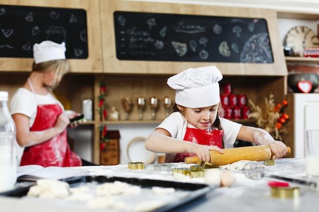 Pequeno chefe. menina encantadora se diverte fazendo biscoitos de massa em uma cozinha aconchegante Foto gratuita