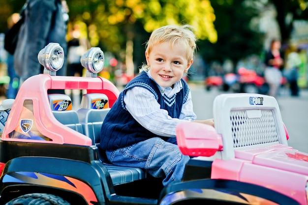 Pequeno e bonito. o homem pequeno considerável conduz o outlander do brinquedo Foto gratuita