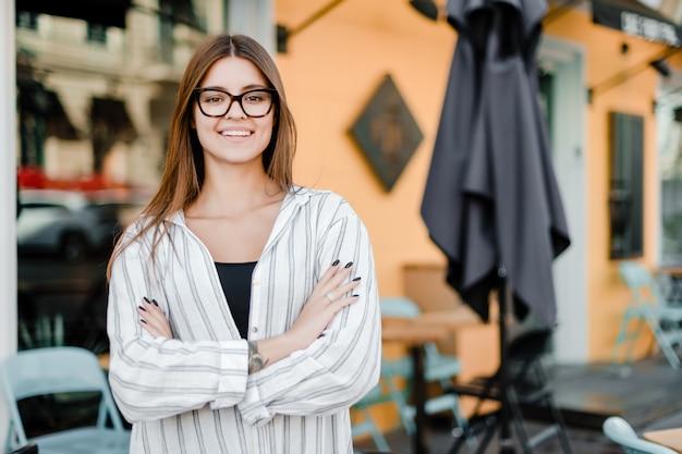 Pequeno empresário em frente a um café sorrindo Foto Premium