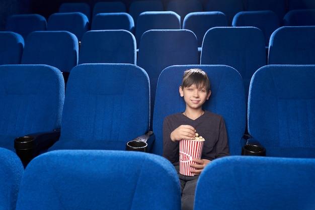 Pequeno espectador masculino sentado sozinho no cinema e sorrindo Foto gratuita