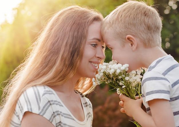 Pequeno filho dá sua mãe um buquê de flores delicadas. Foto Premium