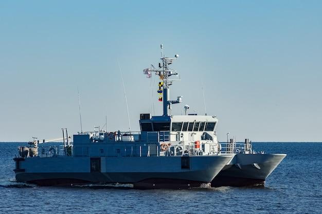 Pequeno navio militar cinza saindo do mar báltico Foto Premium