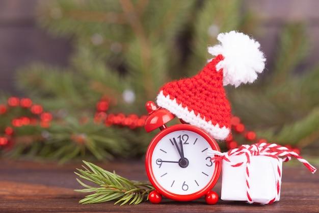 Pequeno relógio em um boné de natal. Foto Premium