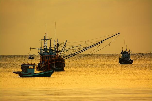 Pequenos barcos de pesca no mar mar na hora do crepúsculo Foto Premium