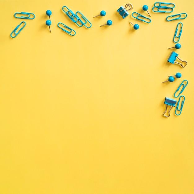 Pequenos clipes e alfinetes azuis para papel Foto gratuita