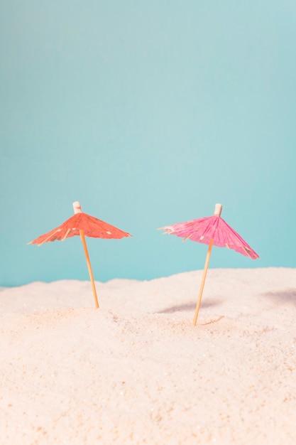 Pequenos guarda-chuvas para bebidas na areia Foto gratuita