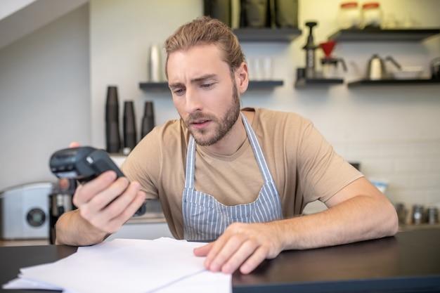 Pequenos negócios. jovem esperto barbudo focado de avental contando os lucros e despesas de seu café Foto Premium