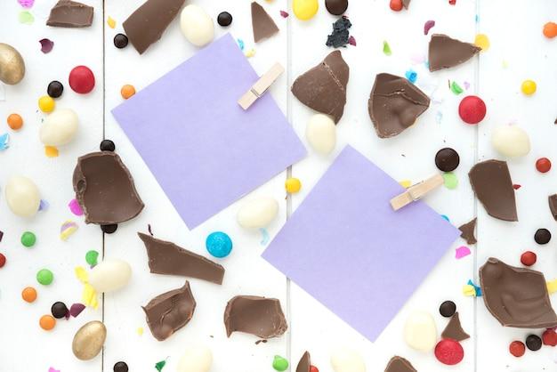 Pequenos papéis com chocolate e doces na mesa Foto gratuita