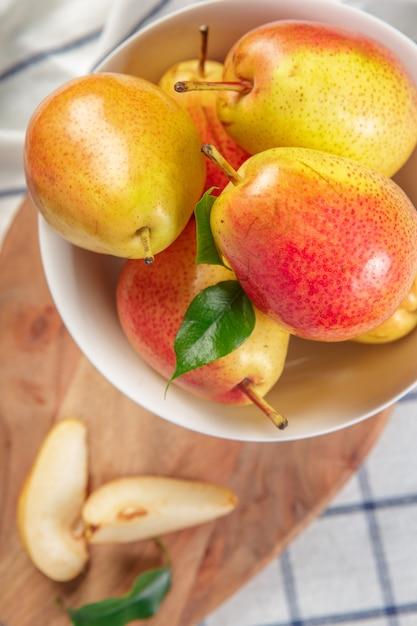 Peras orgânicas estabelece em um pano de cozinha levemente pontilhada Foto Premium