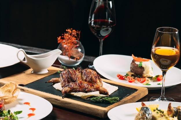 Perdiz grelhada, robalo, tártaro. pratos diferentes em cima da mesa no restaurante. Foto Premium