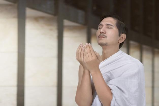 Peregrino asiático bonito do hajj que praying Foto Premium