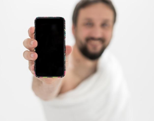 Peregrino masculino muçulmano com telefone móvel Foto Premium