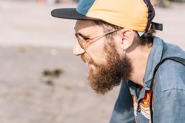 Perfil de um menino ruivo com barba e boné vestindo uma camisa jeans estampada Foto Premium