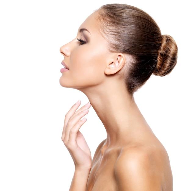 Perfil de uma bela jovem com pele limpa e fresca tocando suavemente seu pescoço, isolado no branco Foto gratuita