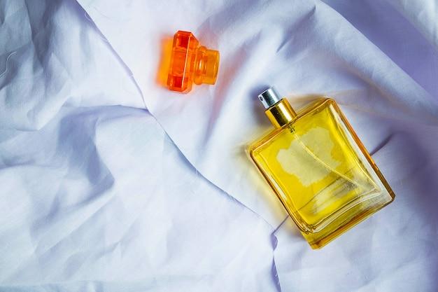 Perfume e frascos de perfume em um assoalho de pano branco Foto Premium