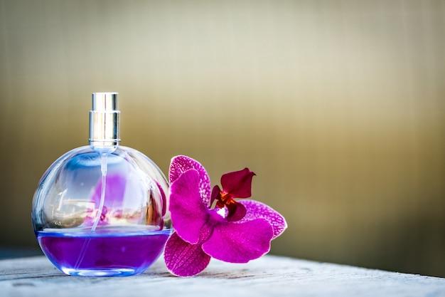 Perfume feminino em linda garrafa com orquídeas em bokeh de fundo. Foto Premium