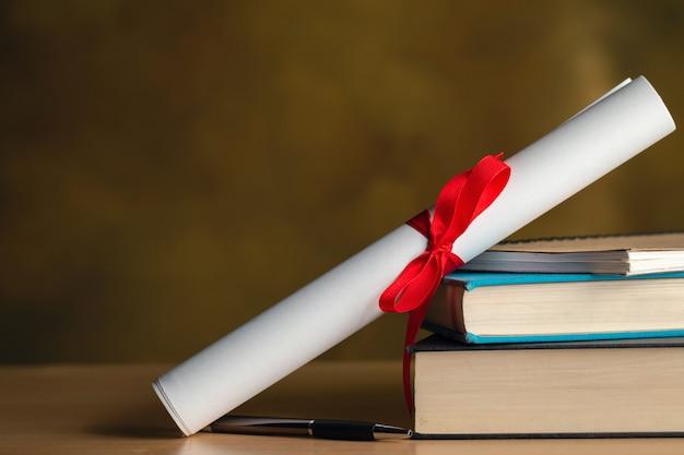 Pergaminho de certificado, livros, caneta na mesa de madeira com copyspace Foto Premium