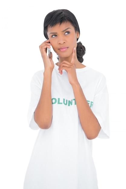 Perguntando voluntário de cabelo preto chamando alguém com seu telefone celular Foto Premium