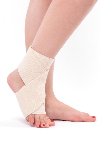 Perna da mulher amarrada com uma atadura elástica, tornozelo pé Foto Premium