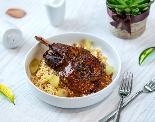 Perna de frango assado com molho servido na bulgur com picles Foto gratuita