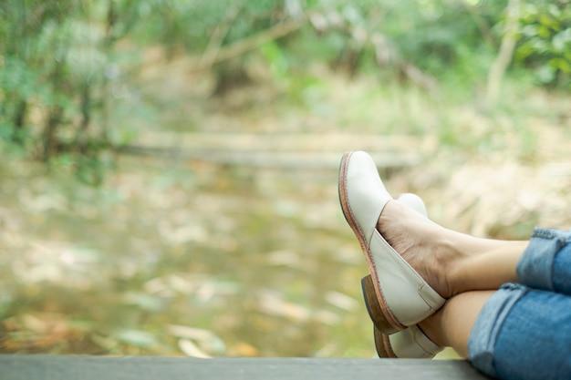 Perna de mulher e sapato que sentado no cais de madeira Foto Premium