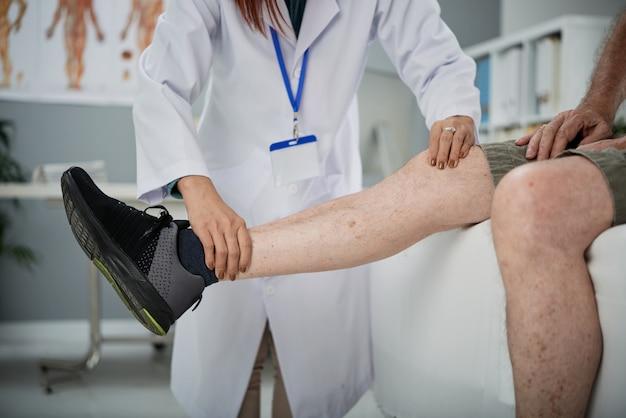 Perna palpadora fisioterapeuta Foto gratuita