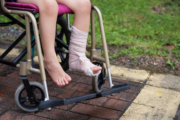 Perna quebrada criança sentar na cadeira de rodas Foto Premium