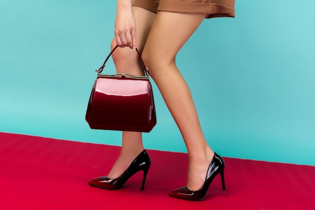 Pernas bem torneadas de mulher usando sapatos de salto alto laqueado preto com bolsinha vermelha. vista de perto Foto Premium