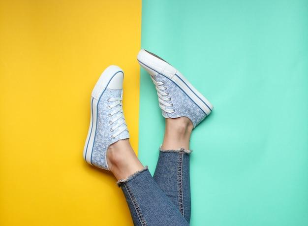 Pernas das mulheres em jeans apertados, rasgados, tênis em amarelo azul pastel. vista do topo Foto Premium