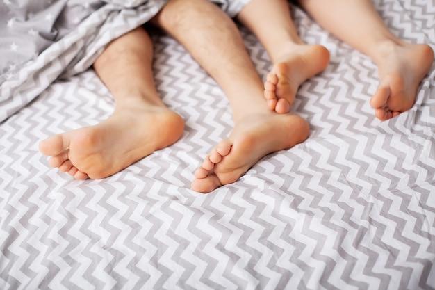 Pernas de amantes sob o cobertor. casal feliz se divertindo na cama Foto Premium