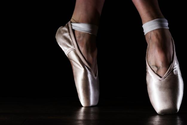 Pernas de bailarina clássica close-up em pointes no chão preto Foto Premium