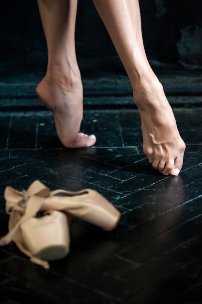 Pernas de bailarina close-up e pointes no chão de madeira preto Foto gratuita