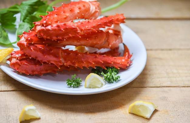 Pernas de caranguejo do alasca rei cozido marisco com especiarias limão na chapa branca na mesa de madeira - Foto Premium