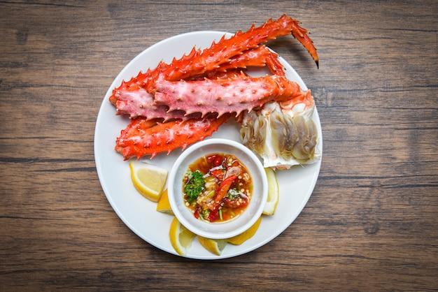 Pernas de caranguejo do alasca rei cozido marisco com molho de limão na chapa branca - vermelho caranguejo hokkaido Foto Premium