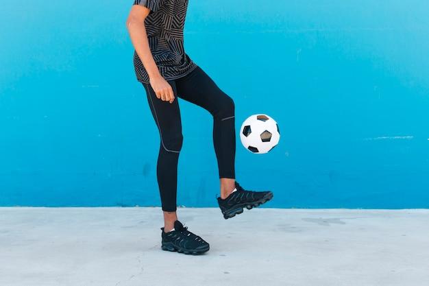 Pernas de colheita do esportista chutando a bola de futebol Foto gratuita