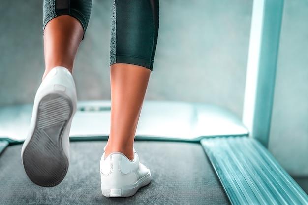 Pernas de corredor interno estão caminhando lentamente na esteira para exercícios leves fechados. Foto Premium