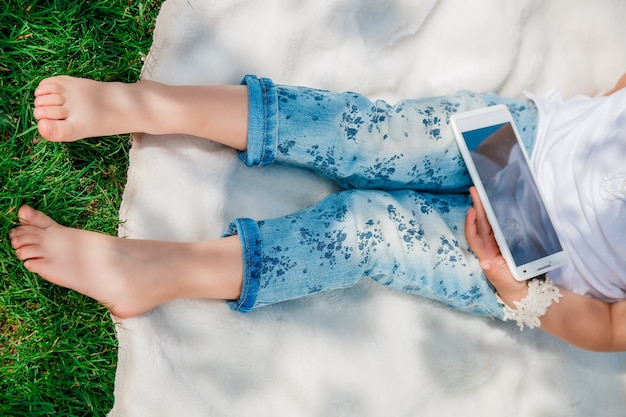 Pernas de criança com tablet, smartphone, telefone para brincar e educação, vista superior. menina irreconhecível. Foto Premium