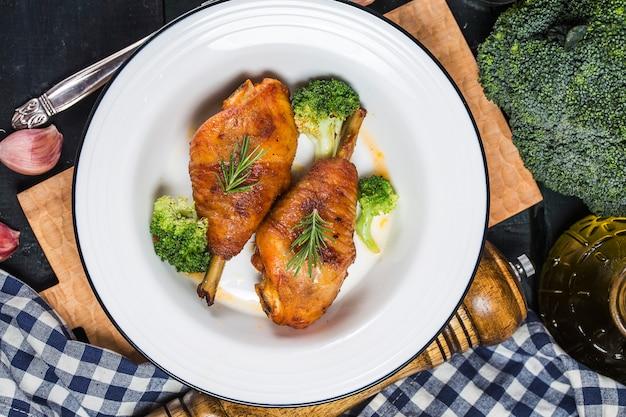 Pernas de frango com legumes na mesa de madeira. Foto Premium