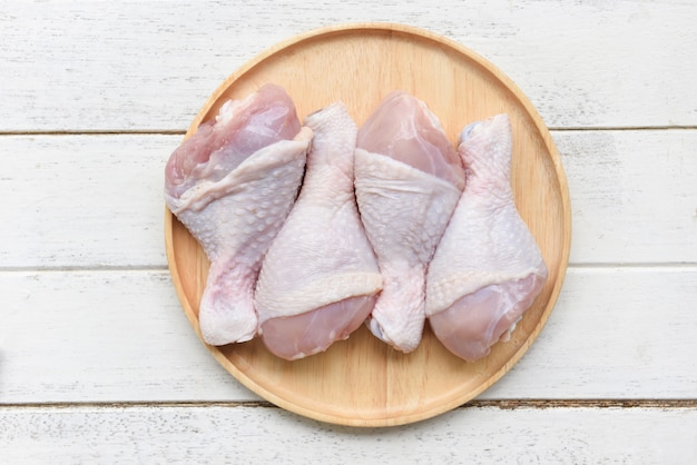 Pernas de frango cru na placa de madeira / carne de frango cru fresco para cozinhar Foto Premium