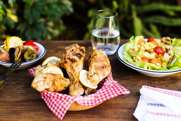 Pernas de frango e salada servida ao ar livre Foto gratuita