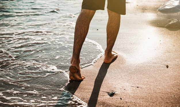 Pernas de homem andando na praia perto da água Foto gratuita
