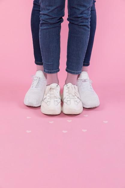 Pernas de homem e mulher de jeans e tênis perto de corações decorativas Foto gratuita