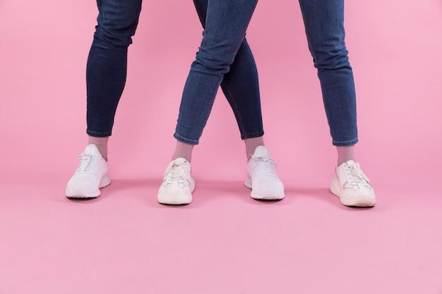 Pernas de homem e mulher em jeans e tênis Foto gratuita