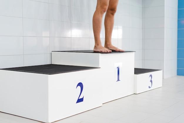 Pernas de homem em pé no pódio da primeira posição Foto gratuita