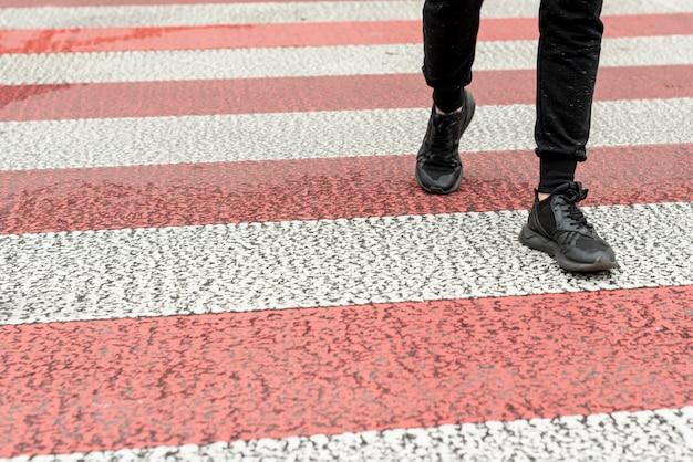 Pernas de homens close-up, passando uma faixa de pedestres Foto gratuita