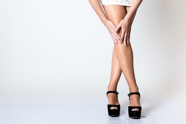 Pernas de linda jovem posando com tela branca Foto gratuita