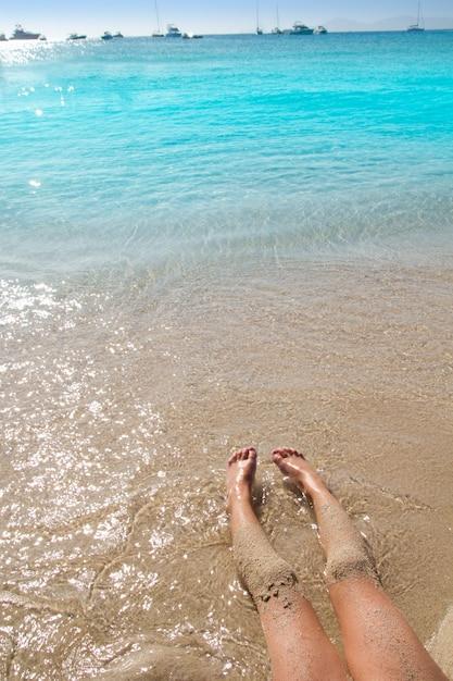 Pernas de menina de crianças na costa de areia da praia Foto Premium