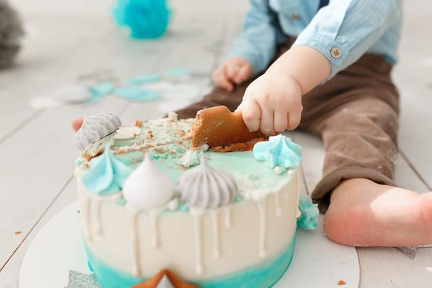 Pernas de menino caucasiano de aniversário e braços enquanto ele destrói e esmaga seu bolo de creme Foto gratuita