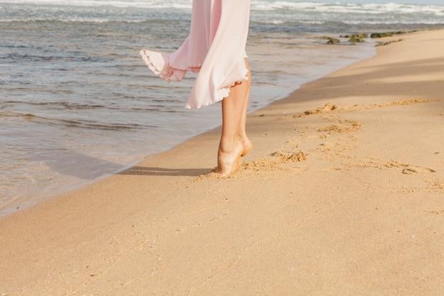Pernas de mulher caminhando na areia da praia Foto gratuita