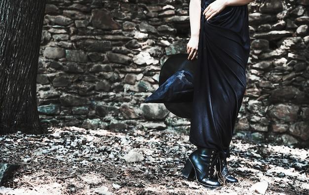 Pernas, de, mulher, em, vestido longo, segurando, chapéu bruxa Foto gratuita